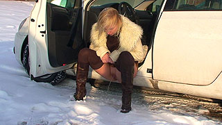 Samantha is so desperate she has to piss into the snow squatting between cars. No one can see her there but she would not have had time to find a better place anyway without drenching her knickers.